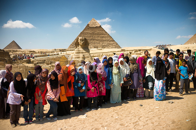 CAIRO, Oct. 5, 2012  A group of Malaysian tourists pose for photos near the Pyramid of Khafre in Cairo, capital of Egypt, on Oct. 5, 2012. Peak tourist season in Egypt runs from mid October to May, during winter and spring. (Credit Image: © Li Muzi/Xinhua/ZUMAPRESS.com)