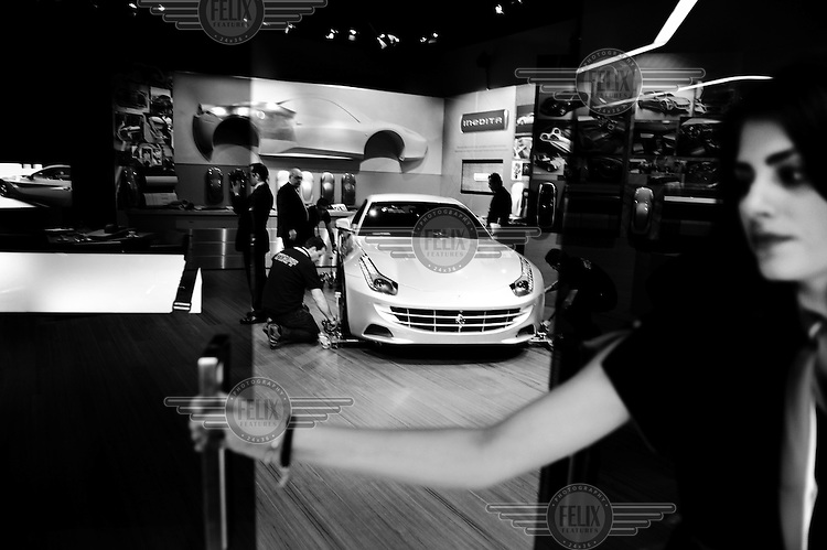 The show staff move a car in the Ferrari Tailor Made showroom, which promotes a new bespoke service, at the Geneva Motor Show.