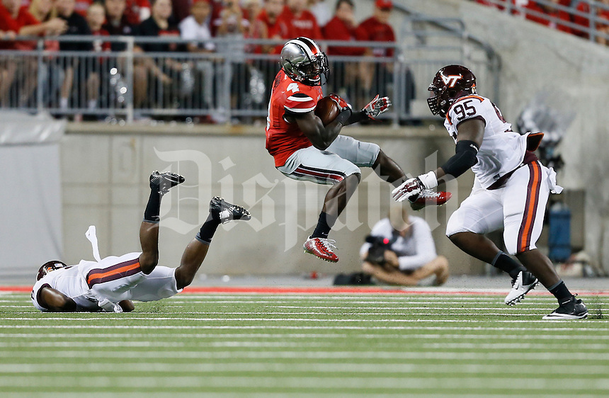 Ohio State Buckeyes running back Curtis Samuel (4) goes for a gain against Virginia Tech Hokies defensive tackle Nigel Williams (95) in the third quarter at Ohio Stadium September 6, 2014. (Dispatch photo by Eric Albrecht)