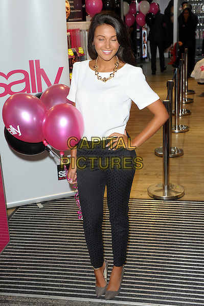 Michelle Keegan<br /> Opens the new Sally Salon in New Oxford street, London, England.<br /> September 12th, 2013<br /> full length white t-shirt black grey gray trousers hand on hip pink balloons eyes closed blinking funny<br /> CAP/CJ<br /> &copy;Chris Joseph/Capital Pictures