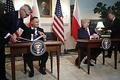 US President Donald J. Trump (R) and Polish President Andrzej Duda (L) participate in a signing ceremony in the Diplomatic Reception Room of the White House in Washington, DC, USA, 12 June 2019. President Trump and President Duda signed an agreement to increase military to military cooperation including the purchase of F-35 fighter jets by Poland and an increased US troop presence in Poland. <br /> Credit: Shawn Thew / Pool via CNP