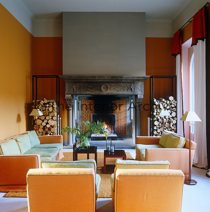 The contemporary furniture and fabrics have created a dramatic contrast to the ancient stone fireplace in the main drawing room of this villa in Tuscany
