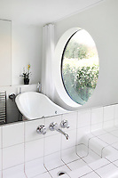 A moden white bathroom with a free-standing roll top bath placed in front of a large circular window.