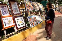 Tourist looking at paintings for sale at the art show held every Sunday in the Jardin del Arte, Sullivan Park, Mexico City