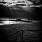 Storm approaching over Bournemouth Pier with Walkers on the beach