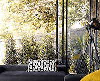 Sliding windows open on to the garden from the contemporary seating area in the living room