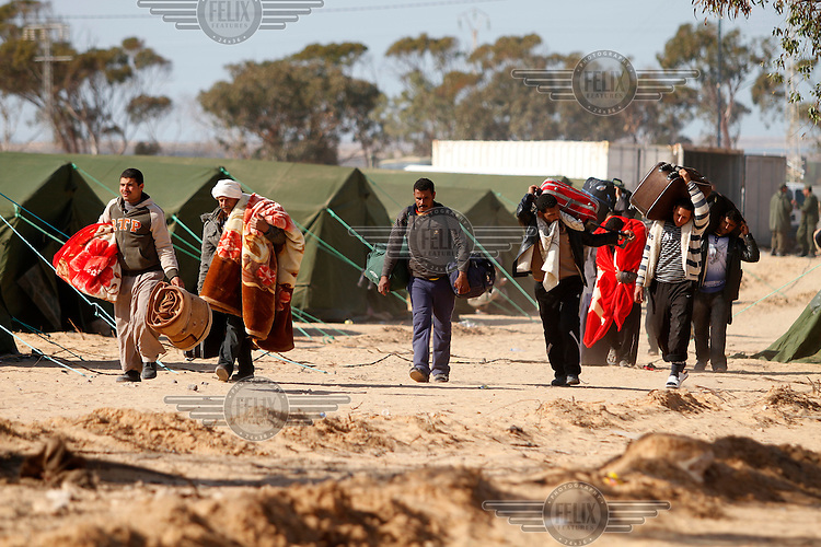 Egyptians entering a refugee camp. Thousands of people, mainly Egyptian workers, flee unrest in Libya and cross the border into Tunisia. Some slept in the open for several days before being processed. .At the same time forces loyal to Col. Gaddafi fought opposition forces in various parts of the country.