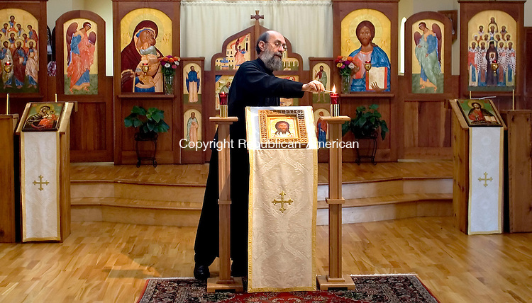SOUTHBURY, CT- 29 SEPTEMBER 2008- 092908JT03-<br /> Rev. Fr. Vladimir Aleandro lights a candle at an icon stand inside the sanctuary of Christ the Savior Greek Orthodox Church in Southbury on Monday.<br /> Josalee Thrift / Republican-American
