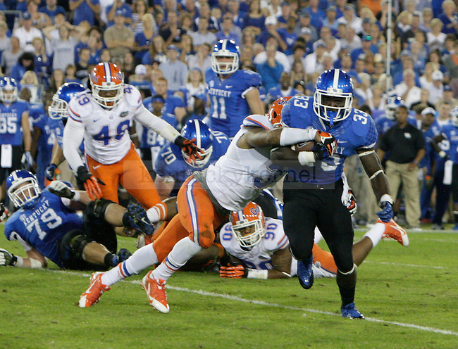 Kentucky Wildcats running back Dyshawn Mobley (33) tries to break a tackle during the first half of the UK Football game against Florida at Commonwealth Stadium in Lexington, Ky., on Saturday, September, 28, 2013. Photo by Jonathan Krueger | Staff