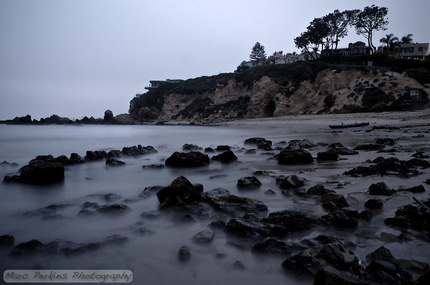 I arrived at Little Corona to do some long-exposure work after sunset, and found a thick marine layer providing a very moody feel to the night. This image is filtered to mute the colors and increase the conrast, providing an almost black-and-white feel to the misty water and rocks, while the bluffs and houses have an old, washed-out look.  This shot is taken about 20 minutes after sunset, so the lights in the houses can be seen as a lone boat sits on the beach.