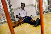A Cuban musician, troubadour (trovador in Spanish), changes strings on his old guitar during the Carnival in Santiago de Cuba, Cuba, 27 July 2008. About 50 years after the national rebellion, led by Fidel Castro, and adopting the communist ideology shortly after the victory, the Caribbean island of Cuba is the only country in Americas having the communist political system. Although the Cuban state-controlled economy has never been developed enough to allow Cubans living in social conditions similar to the US or to Europe, mostly middle-age and older Cubans still support the Castro Brothers' regime and the idea of the Cuban Revolution. Since the 1990s Cuba struggles with chronic economic crisis and mainly young Cubans call for the economic changes.