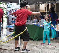 NWA Democrat-Gazette/ANTHONY REYES &bull; @NWATONYR<br /> Sofia Ramirez, 5, watches as her brother Fernando Ramirez, 9, tries a hula hoop Tuesday, Aug. 18, 2015 during a block party and ribbon cutting for the Immigrant Resource Center in Springdale. The Center is the first of five planned for the state. It is a cooperation between Arkansas United Community Coalition and Catholic Charities Immigration Services of Northwest Arkansas and will provide area immigrants with immigration navigation services, leadership development opportunities, and civic integration support. The event introduced the public to the services provided by the center and several other organizations were on hand to distribute information about their organizations.