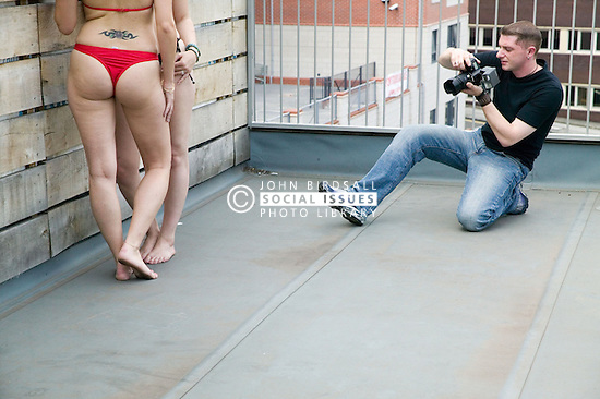 Two Women modelling for a photo shoot on a roof top with a photographer,