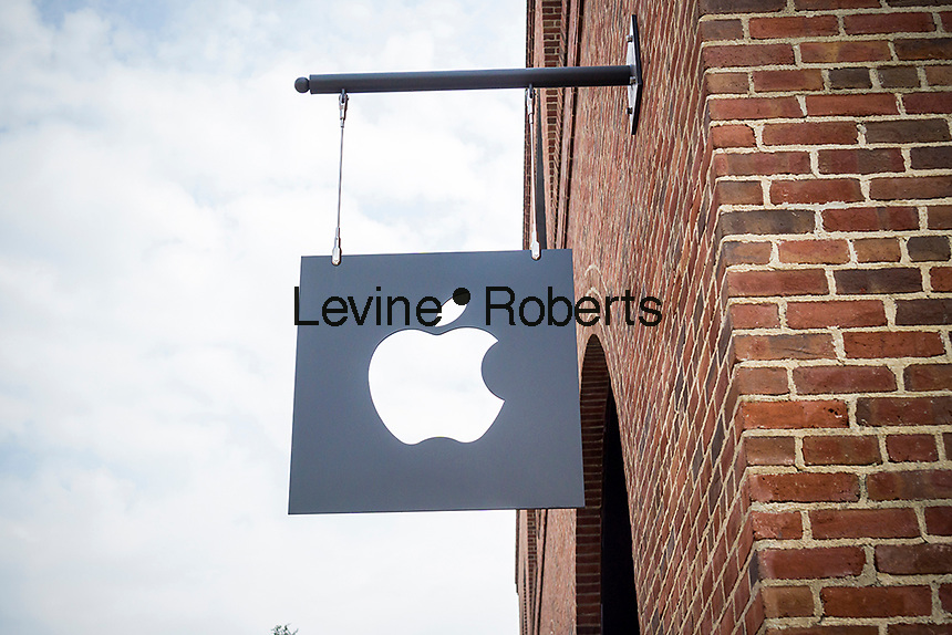 Apple logo sign in Williamsburg, Brooklyn in New York outside of Apple's first store in Brooklyn on Saturday, July 30, 2016. The tech company's new store features exposed brick, giant arch windows and at one story with a brick facade blends in with the neighborhood. Apple gave away commemorative tee-shirts to those attending the grand opening. (© Richard B. Levine)