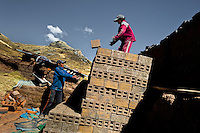 Peruvian boys pile raw bricks aside a kiln at a brick factory in the outskirts of Puno, Peru, 2 August 2012. Child labour is a common practice at the artisanal brick factories, found predominantly in socially deprived areas of the urban zones. Poverty and lack of employment force parents, mainly season workers coming from rural areas of the country, to employ their own children, in an effort to ensure the livelihood for the whole family. Children aged 4-7 take part in simple jobs while children aged 8 and up tend to work regularly, same as adults. A family group, consisting of 2 adults and 2-3 children, may earn 20-25 USD per day, working almost the whole day, often in harsh climatic conditions.