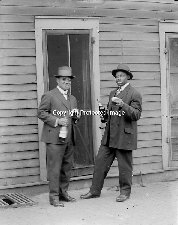 SHARING A DRINK--OR A JOKE? In one image, two friends appear to toast the viewer with a favorite beverage. In the matching view, the same gentlemen pose with casual dignity. Several series of John Johnson photographs raise questions as to their exact purposes, while some were clearly posed as jokes. The man at left in these views may be Clayton Lewis, a star athlete at Lincoln High School who graduated in 1922 and married Dorothy Loving (see image LB200). Clayton (1903-1967) worked as a &quot;red cap&quot; (porter) for the Chicago, Burlington and Quincy Railroad, then for many years was employed by the Lincoln Water Department before moving to Los Angeles in 1960.<br /> <br /> Photographs taken on black and white glass negatives by African American photographer(s) John Johnson and Earl McWilliams from 1910 to 1925 in Lincoln, Nebraska. Douglas Keister has 280 5x7 glass negatives taken by these photographers. Larger scans available on request.