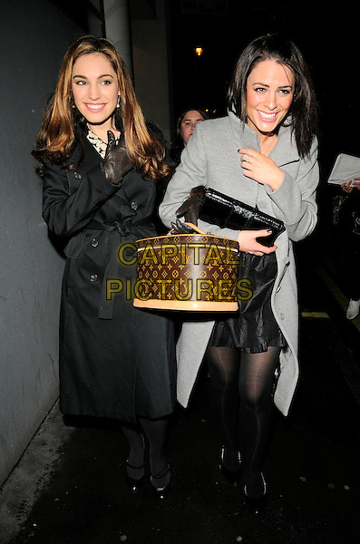 "KELLY BROOK & SUZY AMY .The final performance of ""Fat Pig"" at the Comedy Theatre, Panton Street, London, England, November 29th 2008..full length black coat trench Louis Vuitton vanity case bag leather gloves linked arms arm in arm grey gray tights shoes mary janes patent .CAP/CAN.©Can Nguyen/Capital Pictures"