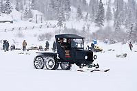 Big game guide and resident of Rainy Pass, Buckey Winkley, is a passenger in his 1924 Ford Model T snowmobile on Puntilla Lake as the top teams rest in the background at the Rainy Pass checkpoint during the 2010 Iditarod