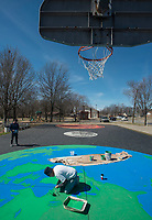 NWA Democrat-Gazette/BEN GOFF @NWABENGOFF<br /> Graham Edwards (left) and Steve Abb work on their mural Thursday, March 8, 2018, on the basketball court at Olive Street Park in Rogers. The Runway Group partnered with Rogers Parks and Recreation to paint the mural titled 'Space Jam: Earth to Mars,' wich shows the Earth under one basket, Mars under the oposite and the moon at center court. Design and painting of the mural is being done by Graham Edwards Art and Abb Custom Painting, with Abb's son Mike Abb also working on the piece.
