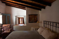 A small rustic bedroom with a beamed wooden ceiling and wrought-iron bedstead