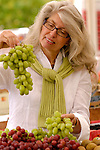 Mature woman holding bunch of grapes