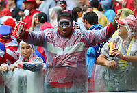 A supporter tries to avoid the torrential rain by wearing swimming goggles