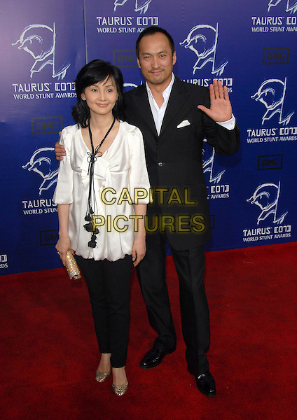 KEN WATANABE & GUEST.The 2007 Taurus Stunt Awards held at Paramount Studios in Hollywood, California, USA..May 20th, 2007.full length black suit white satin top trousers gold clutch purse hand palm waving.CAP/DVS0.©Debbie VanStory/Capital Pictures