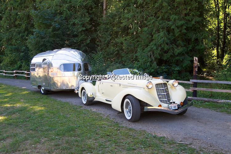 1935 yellow Auburn Boattail Speedster Replicar pulling a 1950 Silver Streak vintage travel trailer.