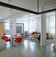 Original orange Eames DAX chairs surround the simple dining table in the open plan living area of this loft apartment