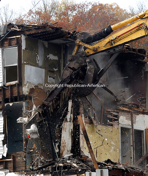 Seymour, CT- 02 November 2014-110214CM03-   Crews demolish the old Seymour Lumber building in Seymour on Sunday. The building, which was declared blighted and containing asbestos, closed down Route 67.  The building located between Route 67 and Little River, required state DOT approval, as well as special fencing to ensure debris didn't fall into the river.   Christopher Massa Republican-American