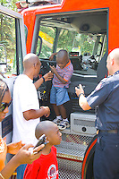 Black dad helps son age 3 from fire engine cab at firefighting demonstration. Aquatennial Beach Bash Minneapolis Minnesota USA
