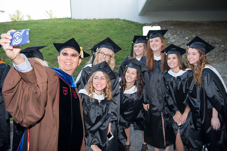 Chao- Yang Lee (Left), Associate Professor in the College of Health Sciences and Professions, take a photo with students at graduate commencement. Photo by Ben Siegel