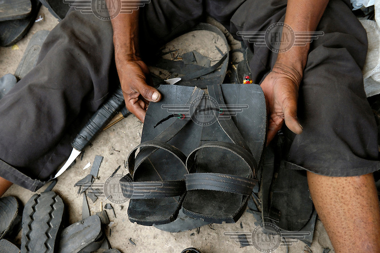 Recycling - David Magomwa making sandals from old truck tyres. He has been making these shoes in the same place, in a busy lane close to Kariakoo market, for 25 years.