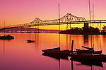 San Francisco Oakland Bay bridge at sunrise and small marina with sailboats silhouetted San Francisco, California USA