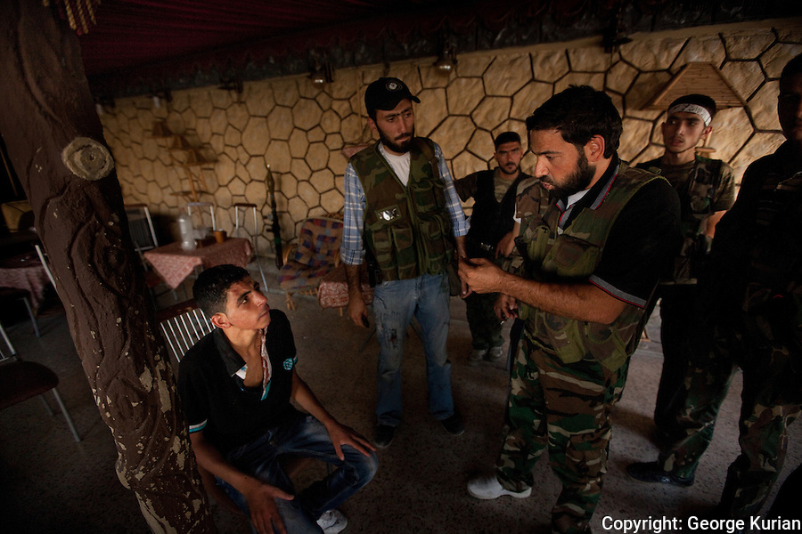 l0/08/20l2, Aleppo: FSA fighters questioning a young man from Selaheddin. He stumbled dazed and bloody, into the nargile cafe turned FSA barracks to tell the rebels that Syrian soldiers had beaten him up to find out whether he was an FSA spy.