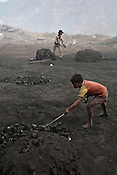 Local residents gather raw coal and process it in Borapahari in Jharia, Jharkhand, India. Coal fires rage just below the surface of the ground, making it too hot to walk with naked feet, noxious gases spew up from fissures, making the environment toxic. Residents who live above the furnace make $2 a day collecting small chunks of coal they sell to illegal middlemen. One or two houses collapse annually into vast underground caverns left unfilled by abandoned mining operations. Photo: Sanjit Das
