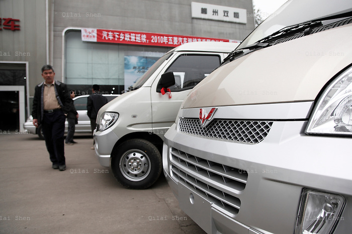 Potential buyers look at SAIC-GM Wuling mini-vans at one of the company's dealerships in Liuzhou, China,on 12 March 2010. Wuling's mini-commercial vehicles topped sales in China last year with over one million units sold.