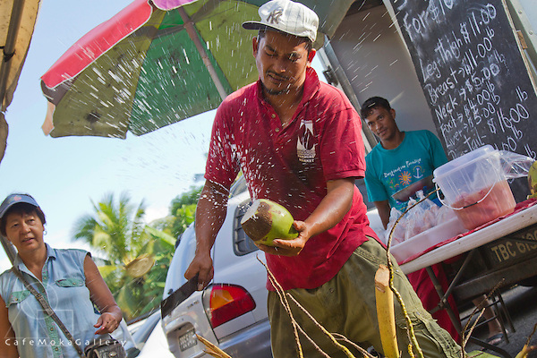 Farmer's Market - fruit and vegetables -Chinese Trinidadian coconut vendor cutting a coconut with a splash -  Diego Martin