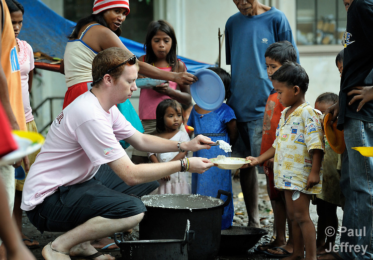 Adam Shaw, a United Methodist mission intern, serves rice to the almost 200 people from the indigenous village of San Fernando who fled their home on March 14, 2012, shortly after the March 5 assassination of Jimmy Liguyon, the baranguay captain. Mr. Liguyon was killed by a paramilitary squad led by Aldy Salusad, which was angered by Liguyon's refusal to sign papers ceding the community's land to a large mining company. Convinced they were also in danger from Salusad and his military allies, his widow and other community members fled to the provincial capital of Malaybalay, where they have set up temporary shelters on the grass in front of provincial offices. They promise not to leave until there is justice in the killing of Liguyon. Shaw is a mission intern assigned to INEACE-Initiatives for Peace in Mindanao..