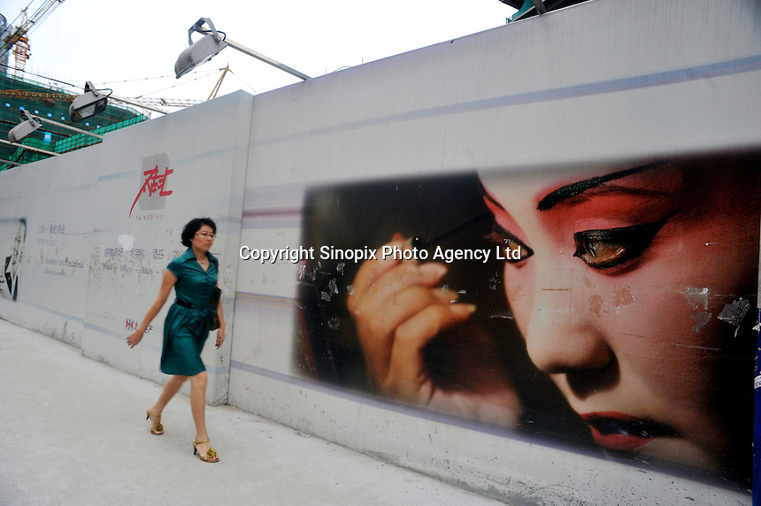 A woman passes a new construction site in Guangzhou, China. .24 Jun 2009