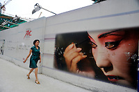 A woman passes a new construction site in Guangzhou, China. .24 Jun 2009