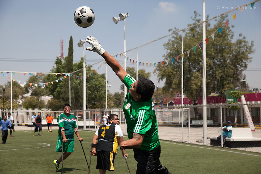 "Rey David Angeles Perez, goalkeeper of Guerreros Aztecas, stretches to claim an attempt on goal during training in Mexico City, Mexico on August 23, 2014. Rey David, 46, lost his left arm in a work accident in 2012. He joined Guerreros Aztecas in September 2013. He is currently unemployed but helps out at his sister's restaurant. Guerreros Aztecas (""Aztec Warriors"") is Mexico City's first amputee football team. Founded in July 2013 by five volunteers, they now have 23 players, seven of them have made the national team's shortlist to represent Mexico at this year's Amputee Soccer World Cup in Sinaloa this December. The team trains twice a week for weekend games with other teams. No prostheses are used, so field players missing a lower extremity can only play using crutches. Those missing an upper extremity play as goalkeepers. The teams play six per side with unlimited substitutions. Each half lasts 25 minutes. The causes of the amputations range from accidents to medical interventions – none of which have stopped the Guerreros Aztecas from continuing to play. The players' age, backgrounds and professions cover the full sweep of Mexican society, and they are united by the will to keep their heads held high in a country where discrimination against the disabled remains widespread. (Photo by Bénédicte Desrus)"