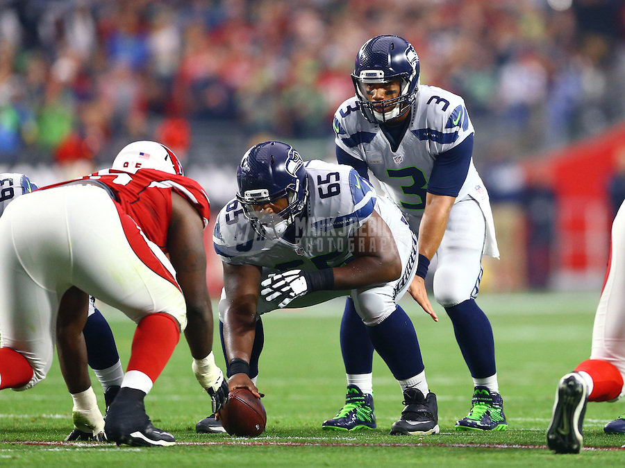 Jan 3, 2016; Glendale, AZ, USA; Seattle Seahawks center Patrick Lewis (65) prepares to snap the ball to quarterback Russell Wilson (3) against the Arizona Cardinals at University of Phoenix Stadium. Mandatory Credit: Mark J. Rebilas-USA TODAY Sports