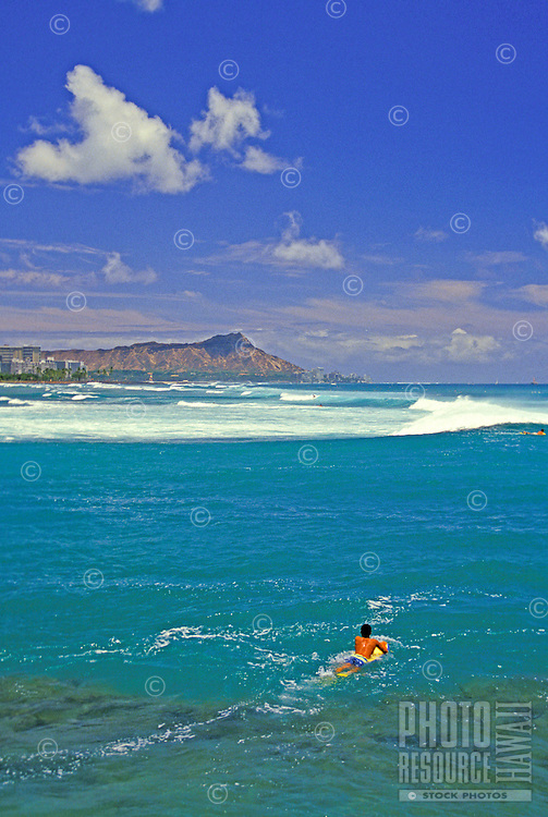 A local surfer paddles out to ride the waves off world famous Waikiki beach with a sweeping view of Diamond Head in the background.