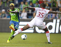 Eddie Johnson, left, of the Seattle Sounders FC takes a shot against the Andrew Jean-Baptiste of the Portland Timbers during play at CenturyLink Field in Seattle Saturday August, 3, 2013. The Sounder won the match 1-0.