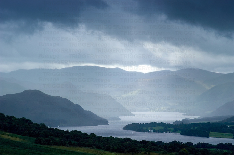 A high view over a lake with mountains and stormy skies