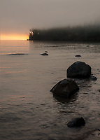 The sunrise glows undfer a lifting fog over Lake Superior from Big Bay State Park o0n Madeline Island in the Apostle Islands, Ashland County, ,Wisconsin