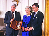 United States President George H.W. Bush and first lady Barbara Bush present the National Medal of Arts to American novelist, poet, short story writer, art critic, and literary critic John Updike during a ceremony in the East Room of the White House in Washington, DC on November 19, 1989. <br />