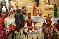 Children are among the workers carrying bricks on their heads at a brick factory.