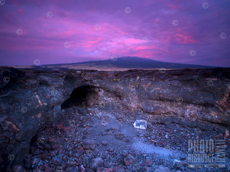 Sunset casts purple and pink light on opening of a large lava tube at the base of Hualalai mountain (dormant shield volcano), Big Island.